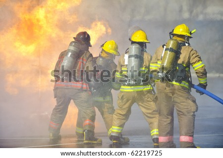 Firefighters attack a propane fire during a training exercise.