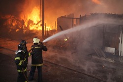 Firefighters combats a fire in houses at a shantytown in Sao Paulo, Brazil.