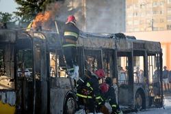 Firefighters crew team extinguish burning coach with foam. Public transit bus had caught fire