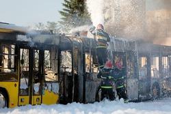Firefighters crew team extinguish burning public transit bus with foam. Rescuers at work