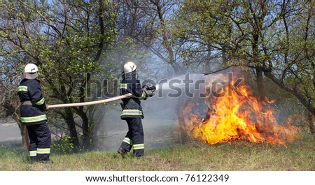 Firefighters extinguish a fire in a forest fire by water flooding