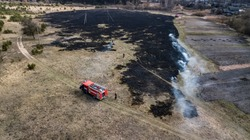 firefighters extinguish dry grass aerial view from a drone
