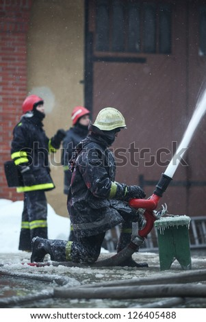 Firefighters extinguishing fire in building