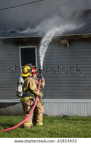 Firefighters fight a fire with a water hose that started in a residential house and someone's home.