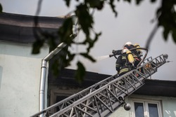 Firefighters on ladders in oxygen masks extinguish the fire in an old house in the middle of the city