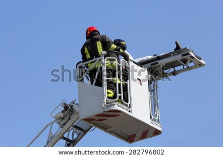 firefighters on the fire truck cage save the wounded person with the stretcher