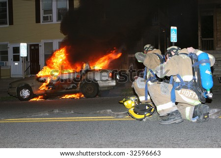 Firefighters prepare to battle car fire