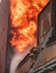 Firefighters put out large massive fire blaze, group of fire men in uniform during fire fighting operation in the city streets, firefighters with the fire engine truck fighting vehicle