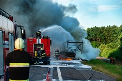 Firefighters put out the fire with foam in the car, fire engine extinguishes a fire on the road