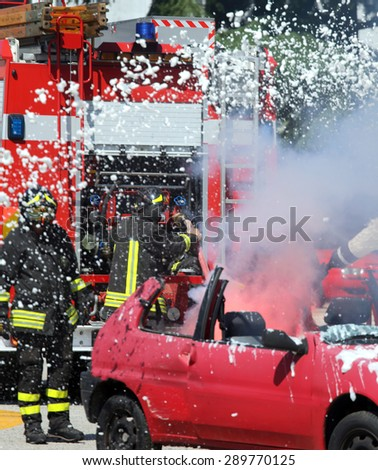 Firefighters put out the fire with white foam in the car
