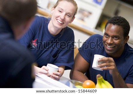 Firefighters relaxing in the staff kitchen - stock photo