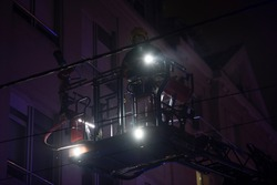 Firefighters rise on a mechanical sliding ladder to the epicenter of the fire. Fighting fire from bucket atop a fire truck. A fireman's crane in action, silhouette against a dark night sky.