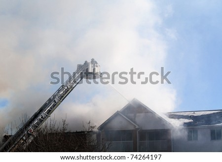 firefighters spraying water on a burning building - stock photo