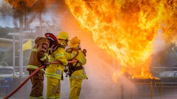 Firefighters training, firemen using water and extinguisher to fighting with fire flame in an emergency situation, under danger situation all firemen wearing firefighter suit for safety.