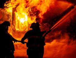 Firefighters use a fire hose to battle intense flames at major emergency fire that destroyed several buildings