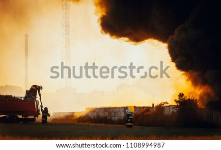 Firefighters with red truck in front of dark smoke from fire stock photo