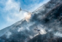 Firefighting Aircraft and Helicopter dropping the water for fighting a fire on mountain, above Lake Ghirla in Valganna, province of Varese, Italy