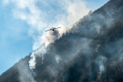 Firefighting Aircraft dropping the water for fighting a fire on mountain above Lake Ghirla in Valganna, province of Varese, Italy