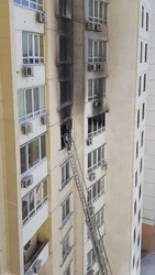 Firefighting ladder to window with black smoke after fire in building. Accidents due arson in protests