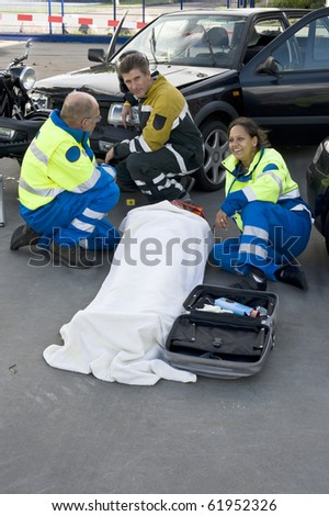 fireman and paramedics sitting behind a victim - stock photo