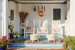 Fireman and patriotic themed worn wooden front porch in Cape Cod with three white rocking chairs and pillows and wicker foot stools and flags and pots of flowers and antique toys