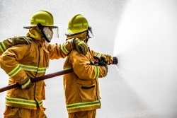 Fireman  attacking a fire with water. firefighter team work.