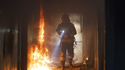 Fireman examining burning corridor during rescue mission