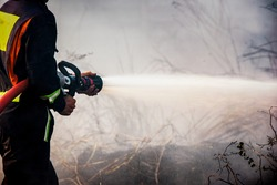 Fireman extinguishes a landfill  in harsh conditions of fire, flames and smoke in the background.