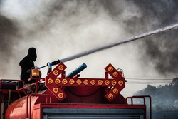 Fireman extinguishes a landfill  in harsh conditions of fire, flames and smoke while on the on fire engine