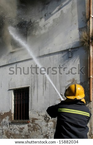 Fireman fighting a fire in a burning building with a water hose
