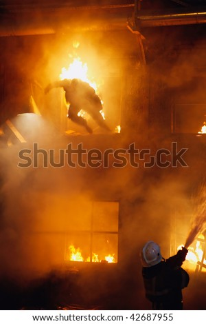 Fireman fighting a fire. The burning man jumps from a window of the second floor.