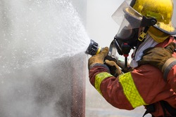 fireman in fire fighting suit spraying water to fire surround with smoke and drizzle