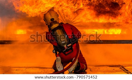 Fireman in helmet and oxygen mask spraying water to fire surround with smoke and drizzle, Firefighter in fire fighting operation, Firefighter using extinguisher and water from hose for fire fighting.