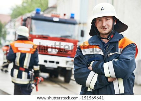 Fireman in uniform in front of fire engine or fire truck during training