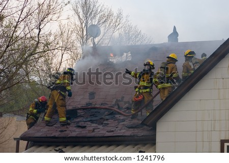 Fireman on a burning roof - stock photo