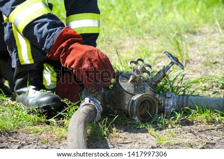 Fireman's hand in glove turning valve of water pump system   #1417997306