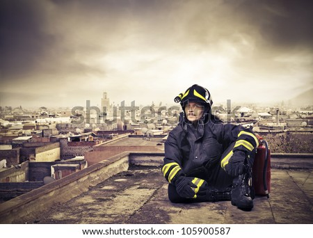 Fireman sitting on the rooftop of a skyscraper over a big city
