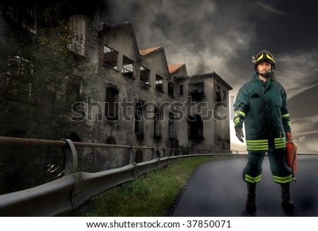 fireman standig near burnt factory - stock photo