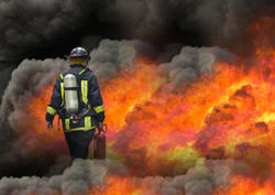 fireman using extinguisher to fighting with fire flame in an emergency situation, under danger situation all firemen wearing fire fighter suit for safety.