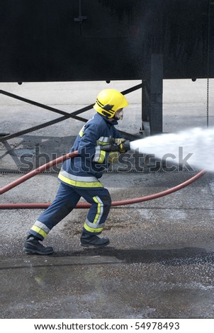 Fireman using water hose