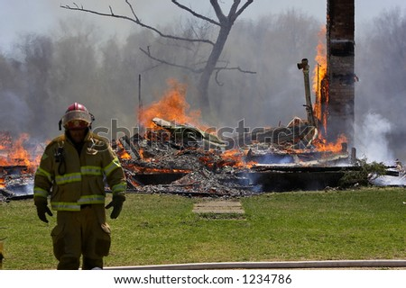 Fireman with burned house