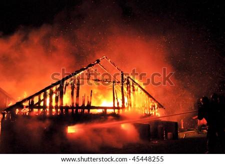 Firemen direct water stream on burning house