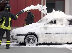 firemen during exercise to extinguish a fire in a car with foam