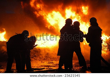 Firemen in a uniform liquidate a heavy fire. - stock photo