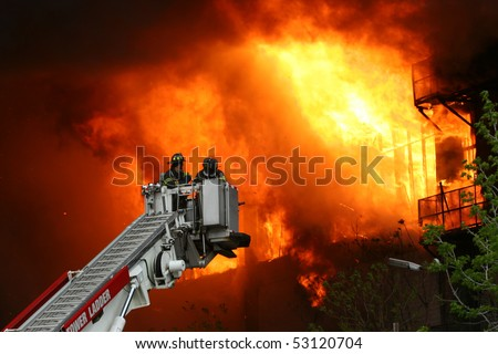Firemen on a crane against wall of fire