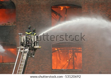 Firemen on a lift up extinguishing fire