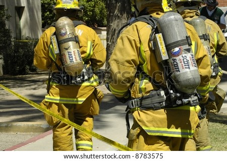 Firemen respond to an emergency wearing air packs