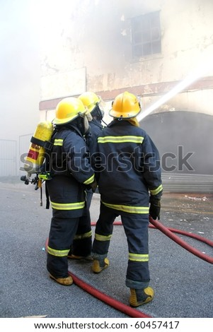 Firemen spraying water onto a burning building