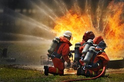 Firemen using extinguisher and water for fight fire during firefight training. All fighter wearing fire suit for safety under danger situation.Fireman work closely with other emergency response agency