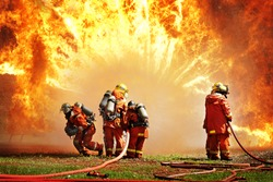 Firemen using extinguisher and water for fighter fire during firefight training. All hero wearing fire suit for safety under danger situation.